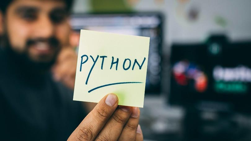 Man holding post-it note with Python written on it